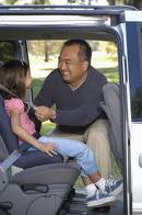 Man Securing a Young Girl into a Safety Seat